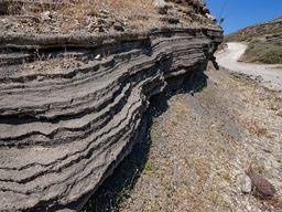 Schichten uralter Ascheablagerungen von diversen Vulkanausbrüchen am Wegrand. Agia Markela/Santorin. (c) Tobias Schorr