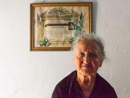 Frau Fani Gavalas vor ihrem Diplom aus 1953, dass ihre Karierre als Schneiderin ermöglichte.