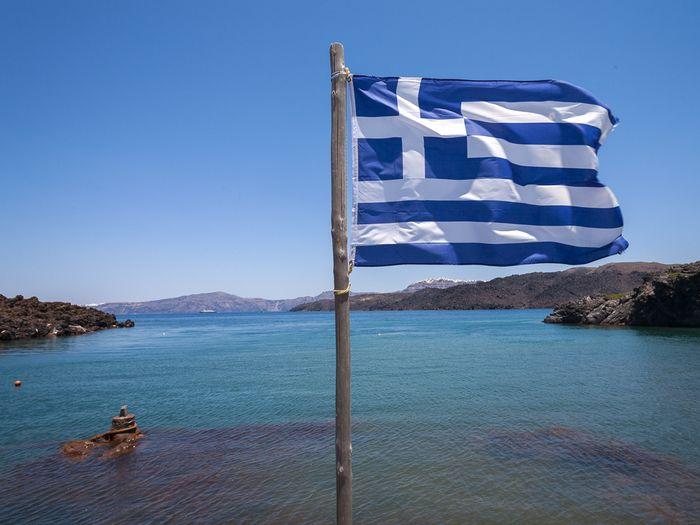 Die griechische Flagge an der Bucht von Palea Kameni/ Santorin. (c) Tobias Schorr