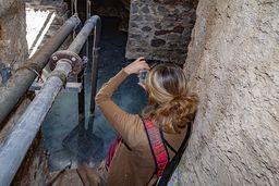 Die Journalistin Alkyone Karamanolis fotografiert die Quelle des Heilbads. (c) Tobias Schorr