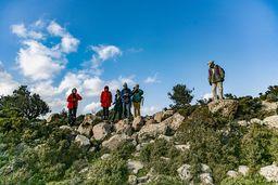 Die Wandergruppe betrachtet eine archäologische Stätte. (c) Tobias Schorr