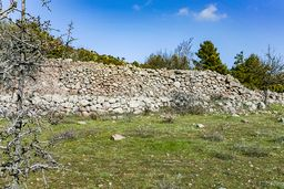 Über die Jahrhunderte haben Bauern die verstreut herumliegenden Reste antiker Gebäude zu einer Trockenmauer aufgetürmt. Wer weiß, was sich darin und darunter verbirgt? (c) Tobias Schorr