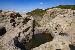 Ehemalige Lavablasen in vulkanischem Gestein, die nun als natürliche Tränke nützlich ist. (c) Tobias Schorr