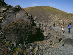 """Die Familie Reimers neben einem Felsen, der zeigt, das er im Inneren gasreich (""""porös"""") war. Vulkan Nea Kameni/Santorin. (c) Tobias Schorr"""