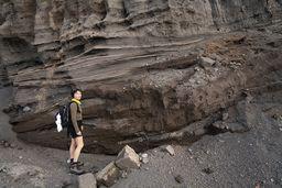 Carmen steht vor den gewaltigen Ascheablagerungen des Nisyros-Vulkans. (c) Tobias Schorr