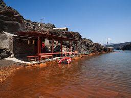 """Sostis Arvanitis hat auf der Insel Palea Kameni eine kleine Terrasse gebaut, in der wir jahrelang unsere Gäste bewirten konnten. Nebendran """"genießen"""" die Touristen für 5 Minuten das warme Wasser der Thermen genießen. (c) Tobias Schorr"""