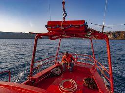 Sostis Arvanitis auf seinem kleinen, orangeroten Boot. Er hat unsere Gruppen über viele Jahre sicher zu den Vulkaninseln von Santorin gebracht. (c) Tobias Schorr